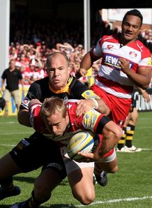 Tim Taylor of Gloucester is tackled by Mark van Gisbergen