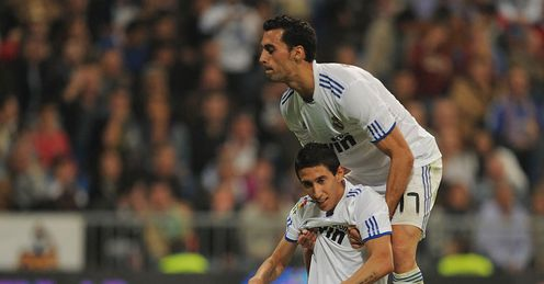 Helping hand: �lvaro Arbeloa helps a flagging Di Maria to his feet in Real's win over Racing