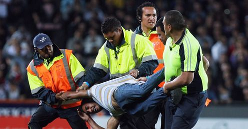 An invader is removed from the pitch at Eden Park