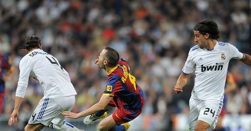 Fall guy: Barcelona's Andres Iniesta is upended at the Bernabeu