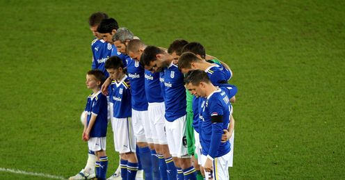 Mark of respect: the players observe a minute's silence at Cardiff in midweek