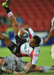 James Kamana of the Lions is tackled by Hurricanes 2012