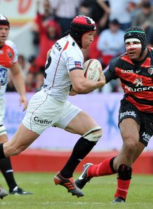 Toulon s centre Matt Giteau C tries to escape Toulouse s Thierry Dusautoir R