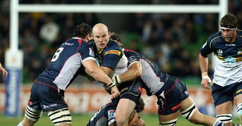 Stephen Moore of the Brumbies is tackled by Rebels