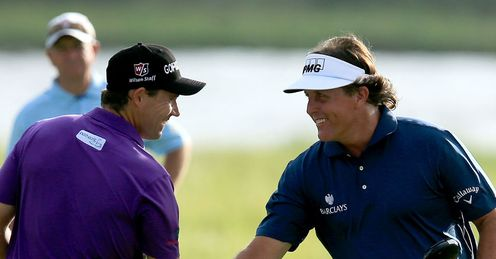 Padraig Harrington (L) and Phil Mickelson shake hands as the prepare to start their second rounds.