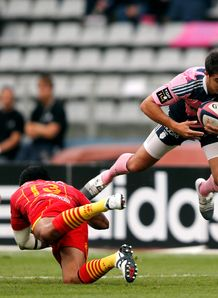 Stade Francais Paris fullback Jerome Porical R is tackled by Perpignan