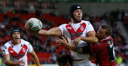 Mark Flanagan C of St Helens passes the ball in the tackle of Stefan Ratchford L and Lee Briers of Warrington