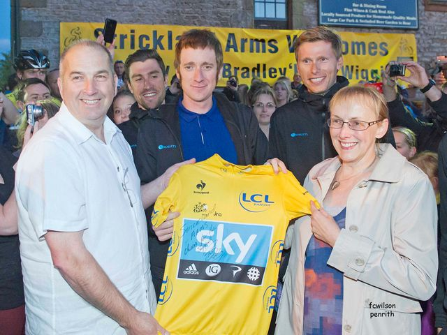 Bradley Wiggins presents a signed yellow jersey