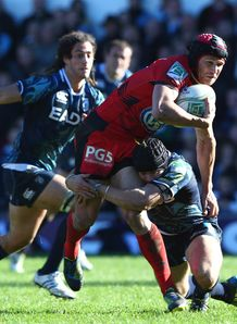 Matt Giteau C of Toulon is held up by Leigh Halfpenny R of Cardiff Blues