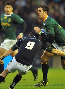 Ruan Pienaar of South Africa is tackledin Scotland