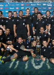 All Blacks standing with Rugby Championship trophy