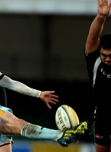 Lee Dickson clearing for Northampton under pressure from Hoani Tui of Exeter