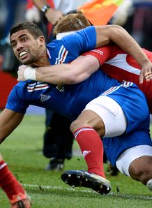 France s right wing Wesley Fofana L is tackled by Wales