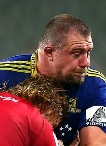 Tony Woodcock of the Highlanders is tackled by Reds