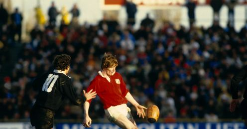 1983 - Ollie Campbell of the British Lions clears the ball upfield as New Zealands Wayne Smith closes in during the second Test