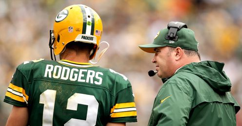 Aaron Rodgers of the Green Bay Packers confers with head coach Mike McCarthy