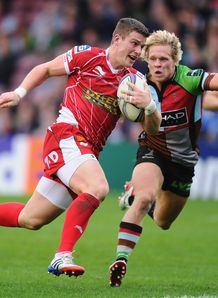 Scott Williams of Scarlets breaks away to score despite the efforts of Matt Hopper of Harlequins