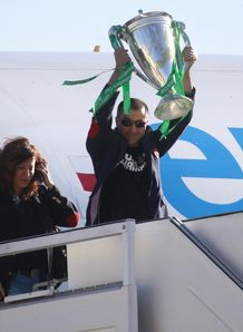 Toulon s rugby team president Mourad Boudjellal C holds the Heineken Cup trophy as he gets off the plane