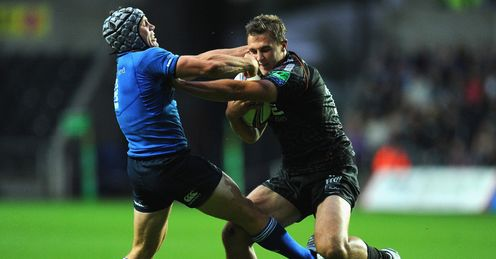 Ospreys player Ashley Beck breaks the tackles of Leinster scrum half Isaac Boss