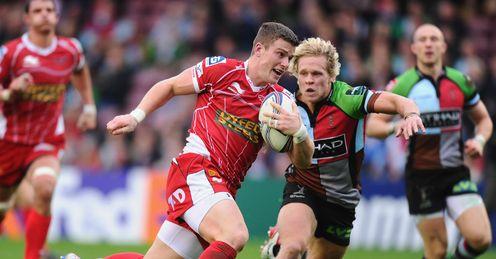 Scott Williams of Scarlets breaks away to score despite the efforts of Matt Hopper of Harlequins
