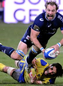 Castres Antonie Claassen top is tackled by Clermont