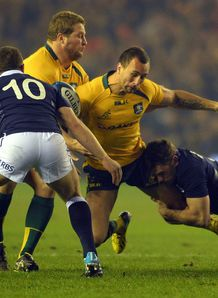 Quade Cooper of Australia is tackled by Scotland