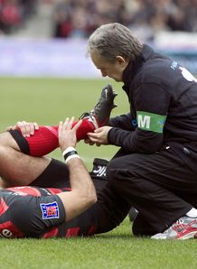 Toulouse s fullback Clement Poitrenaud lays on the field after a knee injury