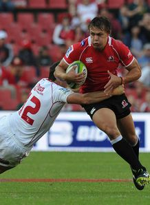 Stefan Watermeyer of Lions is tackled by Mike Harris of Reds