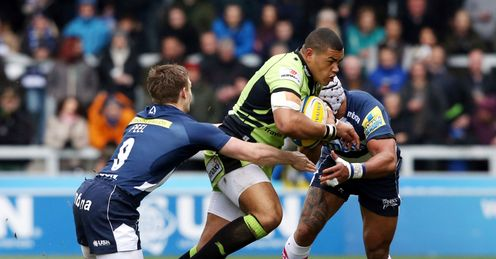 Luther Burrell of Northampton Saints is tackled by Dwayne Peel L and Sam Tuitupou of Sale