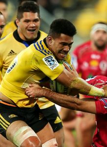 Ardie Savea of the Hurricanes fends Nick Frisby of the Reds on his way to scoring a try
