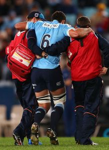 Waratahs captain Dave Dennis helped from the field
