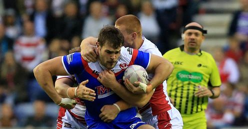 RUGBYL WIGAN ST HELENS' ALEX WALMSLEY IS TACKLED BY WIGAN WARRIORS' JACK HUGHES