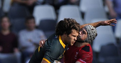 SOUTH AFRICAN CENTRE JAN SERFONTEIN (L) IS TACKLED BY WALES JON DAVIES (R)