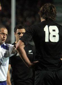 Referee Jonathan Kaplan C shows Sam Whitelock of New Zealand R yellow card